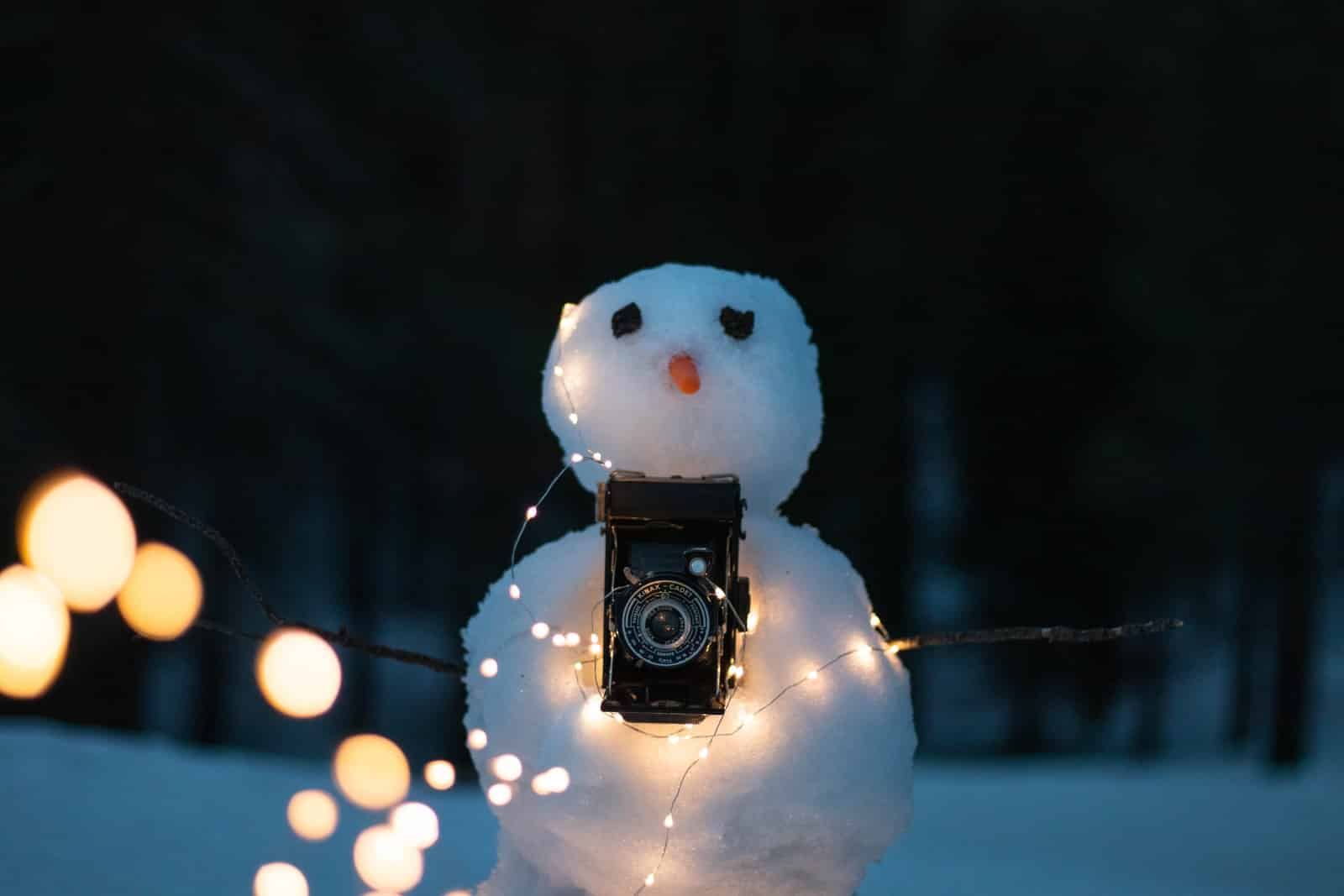 snowman with lighted string lights and black DSLR camera